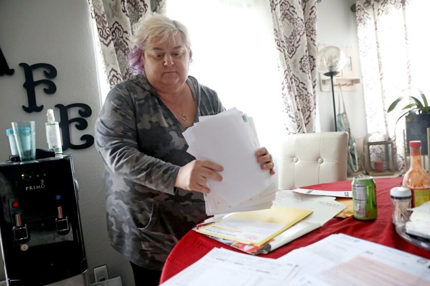 A woman holds a stack of papers at her dining table