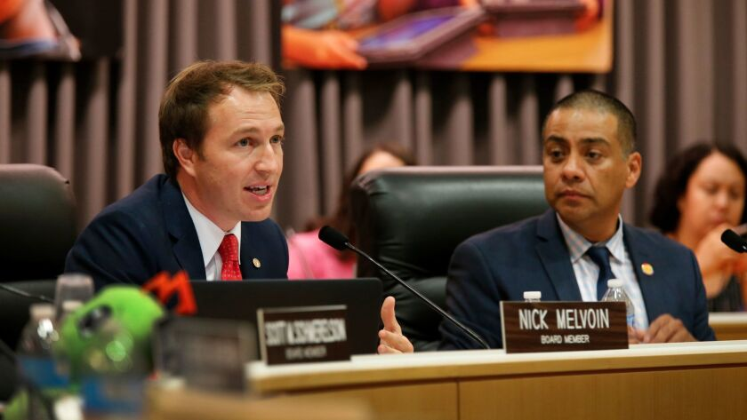 Ref Rodriguez, right, listens to newly sworn-in member Nick Melvoin speak during Thursday's Los Angeles Board of Education meeting.