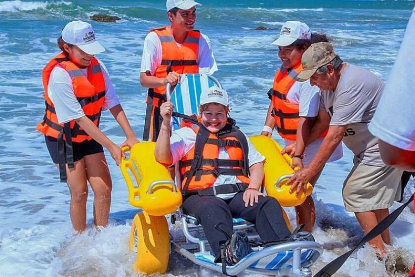 Una mujer con discapacidad posa en una silla modificada para ingresar al mar hoy, jueves 4 de octubre de 2018, en una playa del puerto de Acapulco (México). EFE