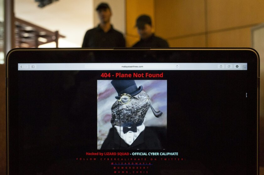 """Workers stand behind a computer which shows the hacked website of Malaysia Airlines, at a cafe in Petaling Jaya outside Kuala Lumpur, Malaysia, Monday, Jan. 26, 2015. The airline's site was changed on Monday, at first with a message saying """"404 - Plane Not Found"""" and that it was """"Hacked by Cyber Ca"""