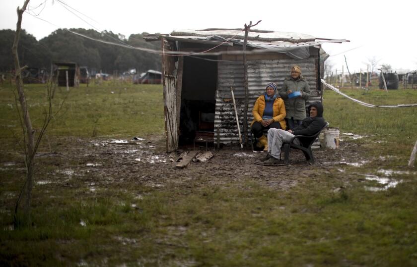 Una familia se sienta afuera de una casa improvisada en un campamento invadido ilegalmente en Guernica