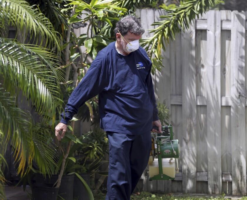 Un inspector de la unidad de control de mosquitos del condado Miami-Dade, en Florida, rocía pesticida en el jardín de una casa en Miami, en ese estado. (AP Foto/Lynne Sladky)