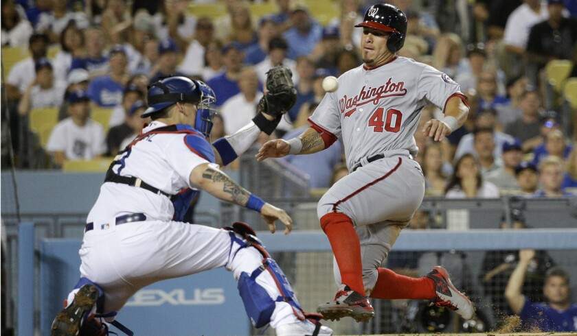 Washington Nationals' Wilson Ramos, right, slides into home plate as he tries to score on a single by Tanner Roark while Dodgers catcher Yasmani Grandal awaits the throw before tagging out Ramos during the eighth inning Tuesday.