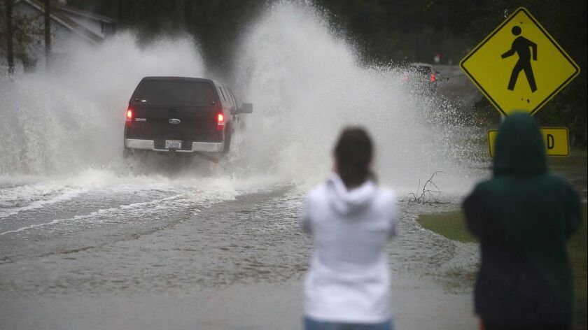 People watch as a truck drives into floodwater in Wilmington, N.C., on Sunday.