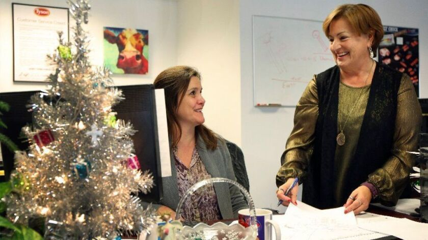 Bobbi Manka, right, works with her colleague Jen Gallois at Tyson Foods in Elgin, Ill. Manka's co-workers helped her after her husband died in 2016.