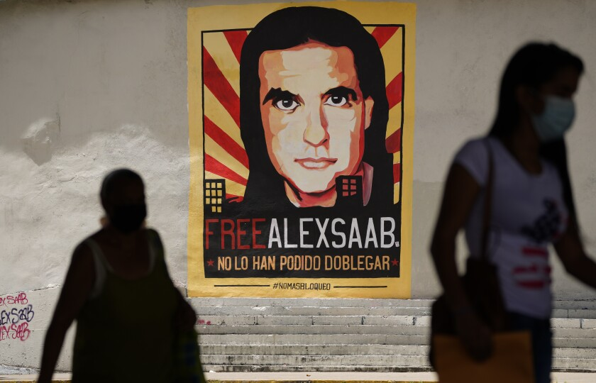 FILE - In this Sept 9, 2021 file photo, pedestrians walk near a poster asking for the freedom of Colombian businessman and Venezuelan special envoy Alex Saab, in Caracas, Venezuela. The Venezuelan government added Saab on Tuesday, September 14, 2021, to the negotiation team that is meeting with the opposition in Mexico. Saab has was detained in Cabo Verde a year ago and is facing extradition to the US for money laundering. (AP Photo/Ariana Cubillos, File)