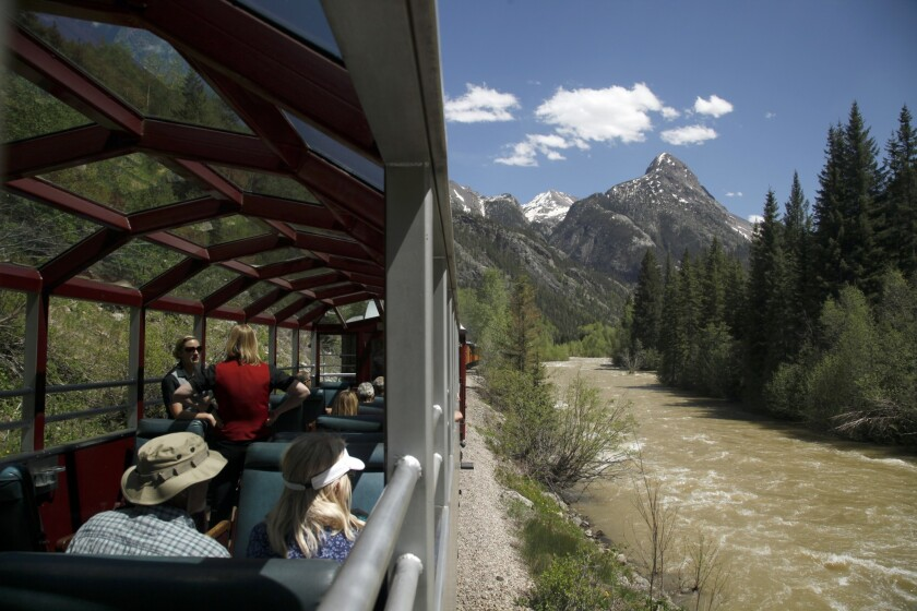 Riders enjoy the scenery aboard the Durango & Silverton Narrow Gauge Railroad as it chugs next to the Animas River on the return trip from Silverton to Durango.