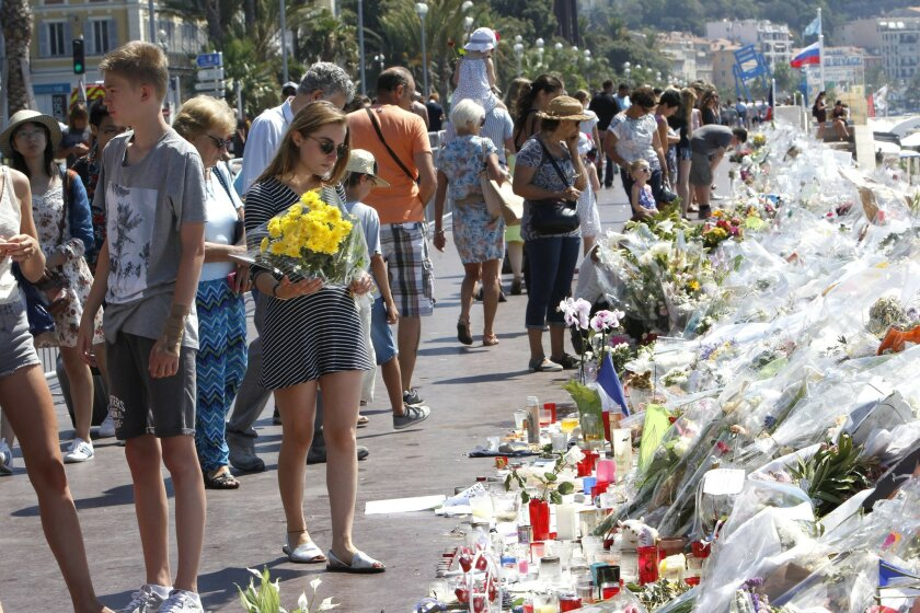 People look at flowers and messages placed along the beach of the Promenade des Anglais in Nice, southern France, Wednesday, July 20, 2016. Joggers, cyclists and sun-seekers are back on Nice's famed Riviera coast, a further sign of normal life returning on the Promenade des Anglais where dozens wer