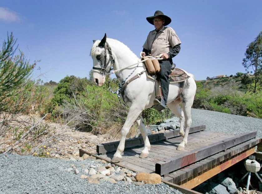 Doug Cruger, a volunteer and vice president of the Bonita Valley Horsemen, and Bow Tie cross a bridge at Otay Valley Regional Park, west of Interstate 805 and north of the U.S.-Mexico border.