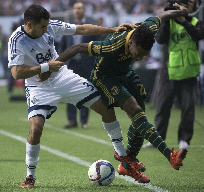 Vancouver Whitecaps FC Steven Beitashour, left, fights for control of the ball with Rodney Wallace, right, of the Portland Timbers during the second half of MLS soccer action in Vancouver, British Columbia, Sunday, Nov. 8, 2015. (Jonathan Hayward/The Canadian Press via AP)
