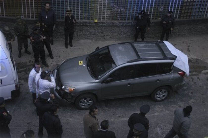Police and forensic experts stand next to a car where two severed heads were found at a street in Mexico City near a major military base, Monday Oct. 3, 2011. A grisly tactic of warring drug gangs that has long affected other parts of the country, the appearance of decapitated heads in the country's capital city has not been seen since January 2008, when two heads were found near the city's international airport. (AP Photo)