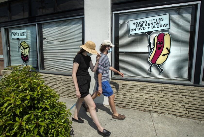 Pedestrians walk past windows with the shades down and an animated hot dog holding a sign advertising Vidiots' offerings.