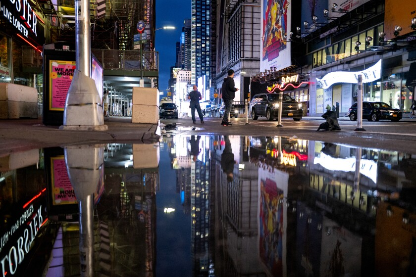 The lights of Times Square in New York are reflected in standing water after flooding.