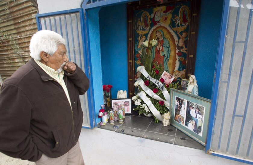 Jose Arias, 83, looks at the religious shrine that he built against the border fence.