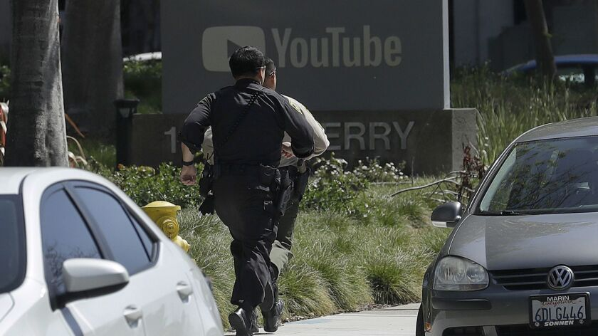 Officers run toward a YouTube office in San Bruno, Calif., Tuesday, April 3, 2018. Police and federa