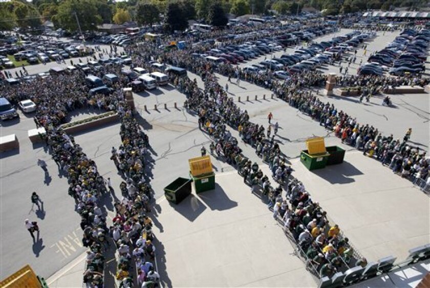 Fans wait to enter Lambeau Field for an NFL football game between the Denver Broncos and the Green Bay Packers, Sunday, Oct. 2, 2011, in Green Bay, Wis. All of the fans are being searched as they enter the stadium. (AP Photo/Mike Roemer)