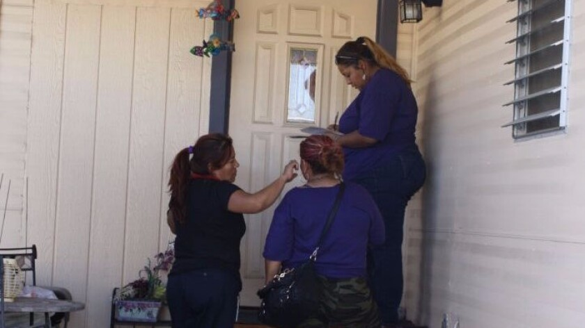 From left, janitors Leticia Soto and Dora Diaz look on as Jasmin Castillo knocks on the door of a mobile home in Las Vegas.