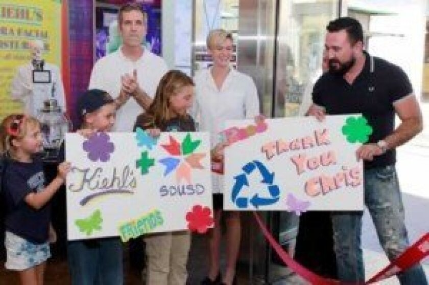 Dr. John Lee Evans, president of the San Diego Unified School Diostrict's Board of Education, and children from Spreckels Elementary, applaud Chris Salgardo (far right) president of Kiehl's USA, for bringing the new recycling bin label program to the county's schools. Photos