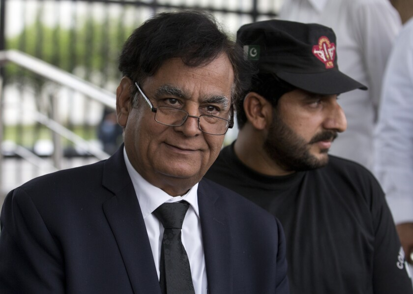 FILE - In this Oct. 8, 2018 file photo, Pakistani lawyer Saiful Malook, left, leaves the Supreme court with a bodyguard, in Islamabad, Pakistan. A Pakistani appeals court on Thursday, June 3, 2021 acquitted a Christian couple sentenced to death on blasphemy charges for allegedly insulting Islam's Prophet Muhammad, their defense lawyer Malook said. (AP Photo/B.K. Bangash, File)