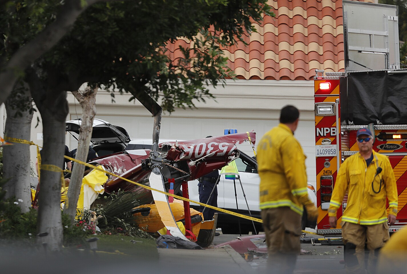 Fire crews work the scene of a helicopter crash that killed three people and injured two others on Shearwater Place in the Bayview Terrace community in Newport Beach.