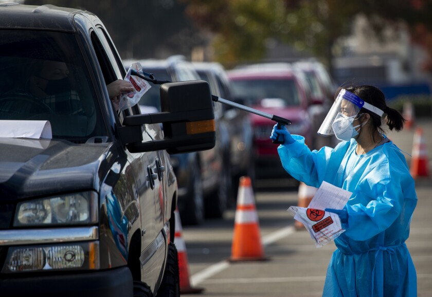 Orange County Health Care Agency personnel conduct testing at the drive-through COVID-19 testing site.