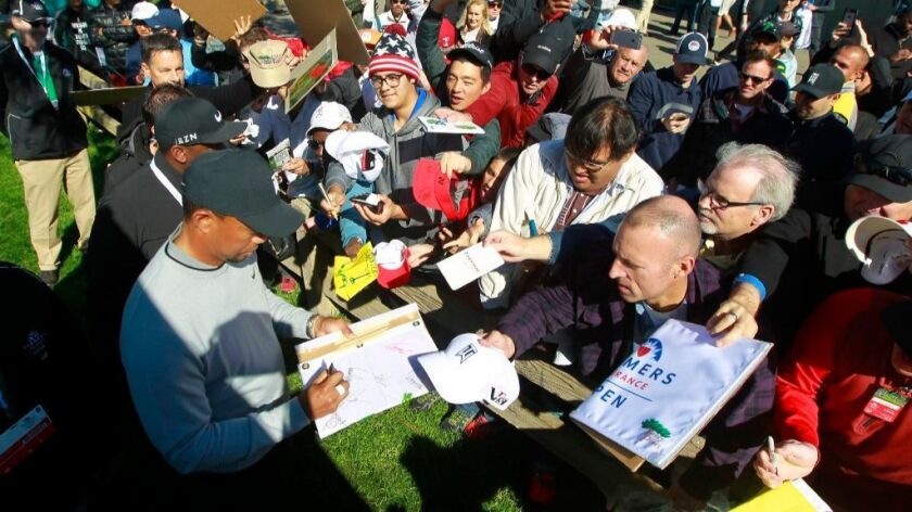 Tiger Woods signs autographs for fans following the Farmers Insurance Open Pro-Am on Jan. 25.