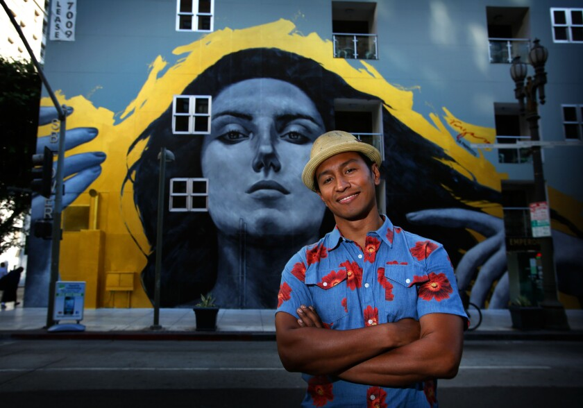 """Robert Vargas stands in front of his downtown mural """"Our Lady of DTLA."""" The City Council could once again allow new murals to be painted."""