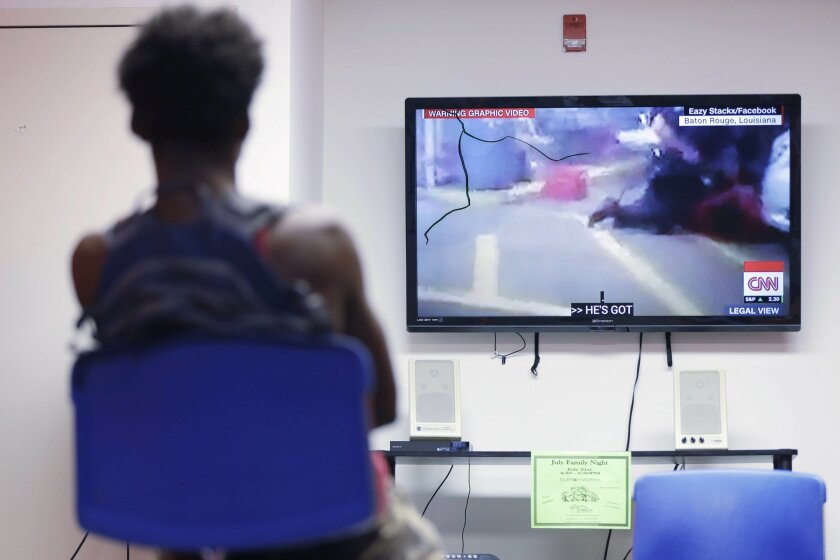 In this July 6, 2016, photo, a teen views a recording of the fatal police involved shooting in Louisiana, during a weekly mentoring meeting at The Bridge, a youth intervention and diversion program in Philadelphia. A group of black boys met with their mentors in Philadelphia to discuss one of the l