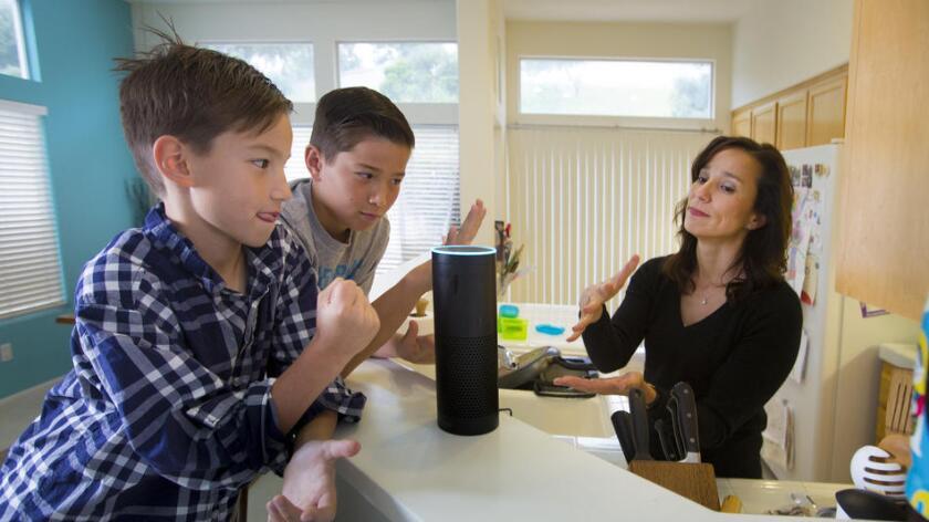 Sutton Philips(i), de ocho años de edad, y su hermano Greyson, de 10, juegan con su mamá Liz y su nueva bocina y asistente personal 'Alexa', de Amazon Echo wireless. Howard Lipin/San Diego Union-Tribune/TNS