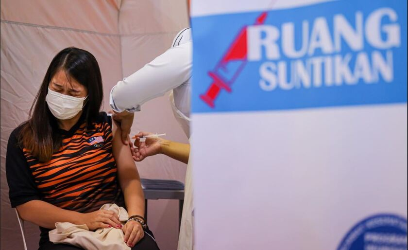 A healthcare worker administers a dose of the Pfizer-BioNTech COVID-19 vaccine to a Malaysian badminton player