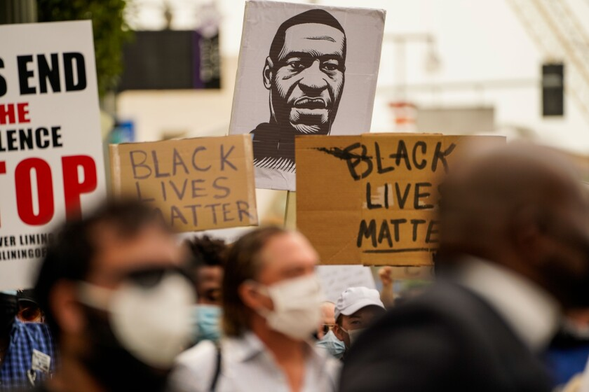 A sign with the likeness of George Floyd is seen at a protest outside L.A. City Hall.