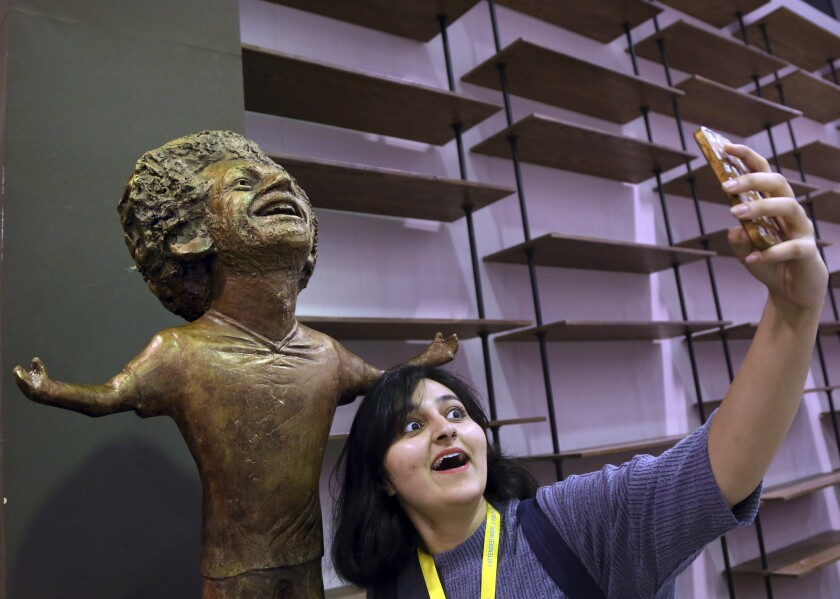 A participant at an international youths gathering poses for selfie with a bronze statue of Liverpool striker Mohammed Salah in a conference hall, in Sharm El Sheikh, Egypt, Monday, Nov. 5, 2018. The statue unveiled in his native Egypt has kicked up a social media storm because of its poor resemblance. It depicts Salah with a disproportionately large head and baby arms stretched in the celebratory pose the 26-year-old Egyptian took in the latter part of last season after scoring goals.