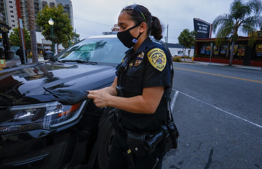 A National City police officer dons protective mask, eye protection and gloves.