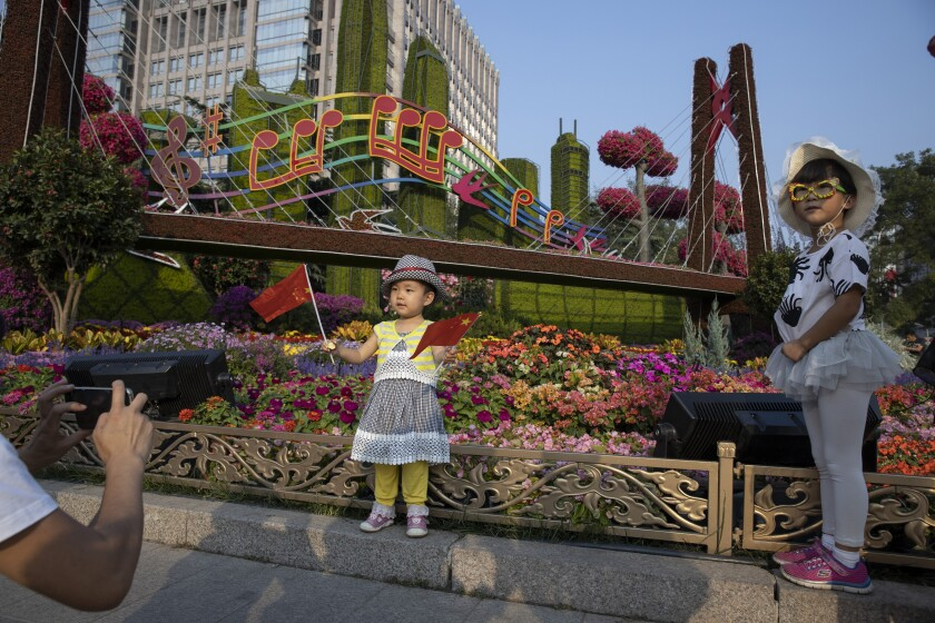 """In this Saturday, Sept. 28, 2019, photo, Chinese children pose with Chinese national flags near a floral display for the upcoming 70th anniversary of the Founding of the People's Republic of China in Beijing. Chinese President Xi Jinping has an ambitious goal for China: to achieve """"national rejuvenation"""" as a strong and prosperous nation by 2049, which would be the 100th anniversary of Communist Party rule. One problem: U.S. Donald Trump wants to make the United States great again too. (AP Photo/Ng Han Guan)"""