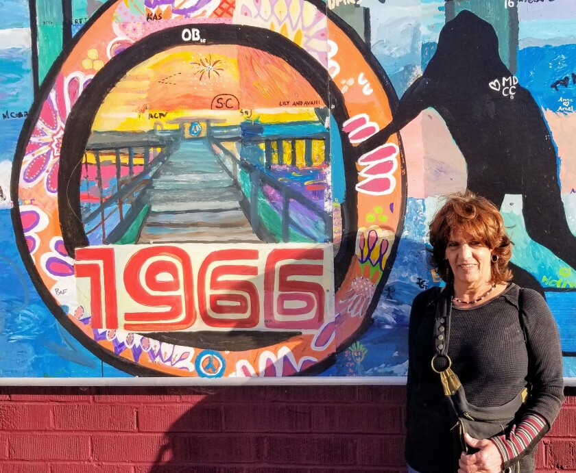 Artist Janis Ambrosiani poses with one of the many OB murals.