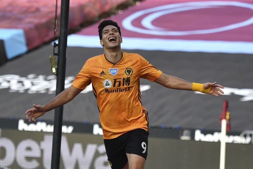 """FILE - In this Saturday, June 20, 2020 file photo, Wolverhampton Wanderers' Raul Jimenez celebrates after scoring his side's first goal during the English Premier League soccer match between West Ham and Wolverhampton at London stadium in London, England. Jimenez has completed his recovery from a fractured skull and is ready to start the new Premier League season with Wolverhampton. The Mexican forward played in a pre-season friendly against third-division Crewe. Wolverhampton wrote on its Twitter account that """"eight months of hard work and rehabilitation have led to this moment."""" Jimenez had surgery in late November after a clash of heads with Arsenal defender David Luiz during a Premier League game. (Ben Stansall/Pool via AP, File)"""