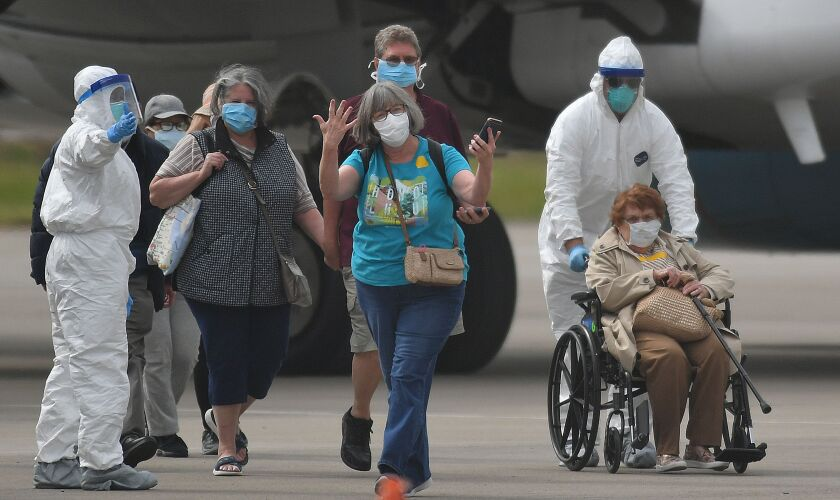 A woman gestures as medical personnel help load passengers from the Grand Princess cruise ship onto airplanes at Oakland International Airport Tuesday.