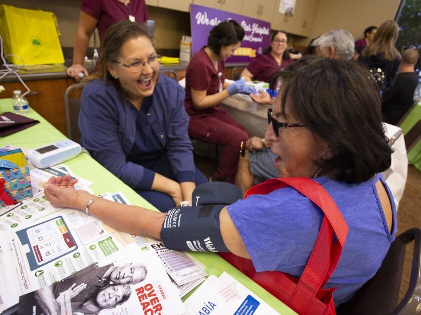 Teresa Bleifus RN, (CQ) del Temecula Valley Hospital se ríe mientras toma la presión arterial de Ana Galarraga (CQ)