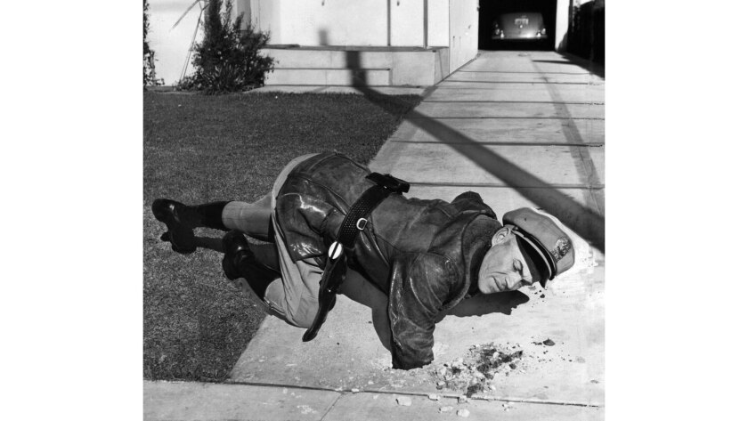 Officer Bobby Clark reaches into a hole caused by a dud antiaircraft shell in a driveway in Santa Monica on Feb. 25, 1942. The shell was recovered.