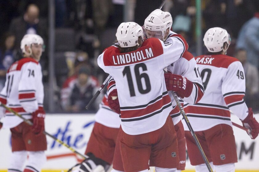 Carolina Hurricanes' Jordan Staal (11) celebrates with teammate Elias Lindholm after scoring the game-winning goal against the Toronto Maple Leafs during overtime in an NHL hockey game Thursday, Jan. 21, 2016, in Toronto. (Chris Young/The Canadian Press via AP)