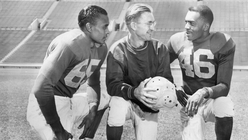 Woody Strode, left, and Kenny Washington, right, with Los Angeles Rams coach Adam Walsh on Sep. 7, 1946.