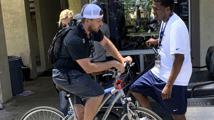 Rams quarterback Case Keenum (on bicycle) chats with team spokesman Artis Twyman on Thursday at UC Irvine.