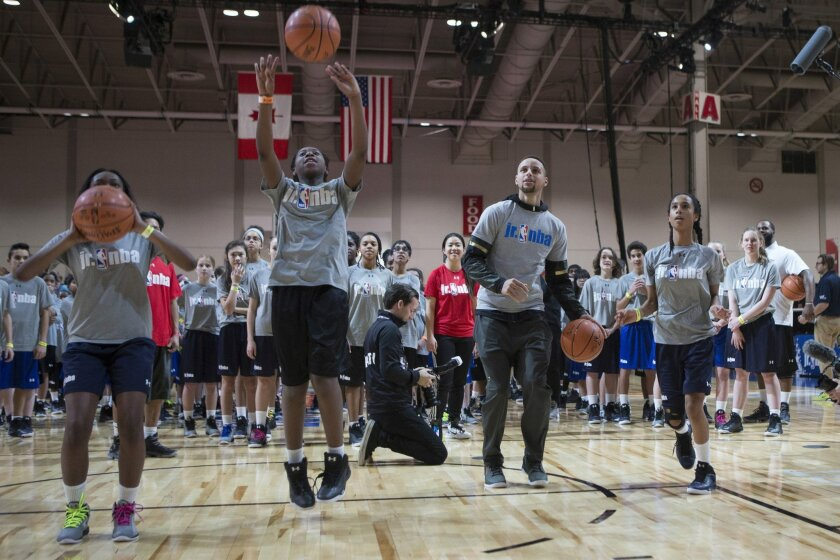 Golden State Warriors point guard Stephen Curry, center right,  takes school children through a skills drill at a Jr. NBA Day event, part of the All-Star festivities in Toronto on Friday, Feb. 12, 2016. (Chris Young/The Canadian Press via AP)