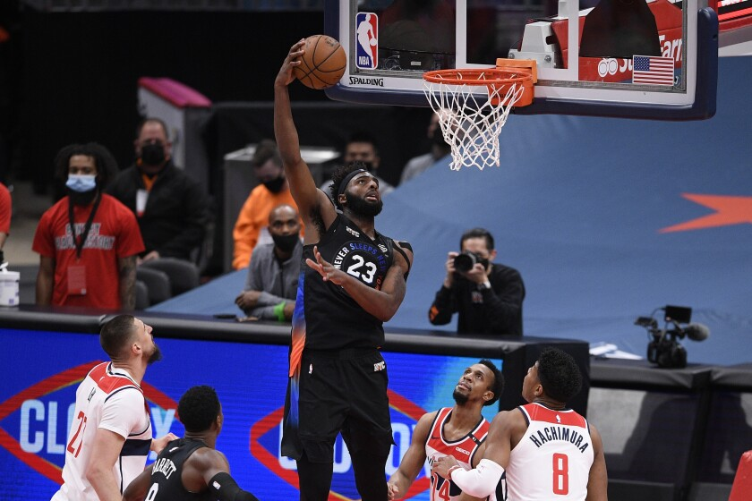 New York Knicks center Mitchell Robinson (23) goes to the basket between Washington Wizards guard Ish Smith (14), forward Rui Hachimura (8) and center Alex Len, left, during the first half of an NBA basketball game, Friday, Feb. 12, 2021, in Washington. (AP Photo/Nick Wass)