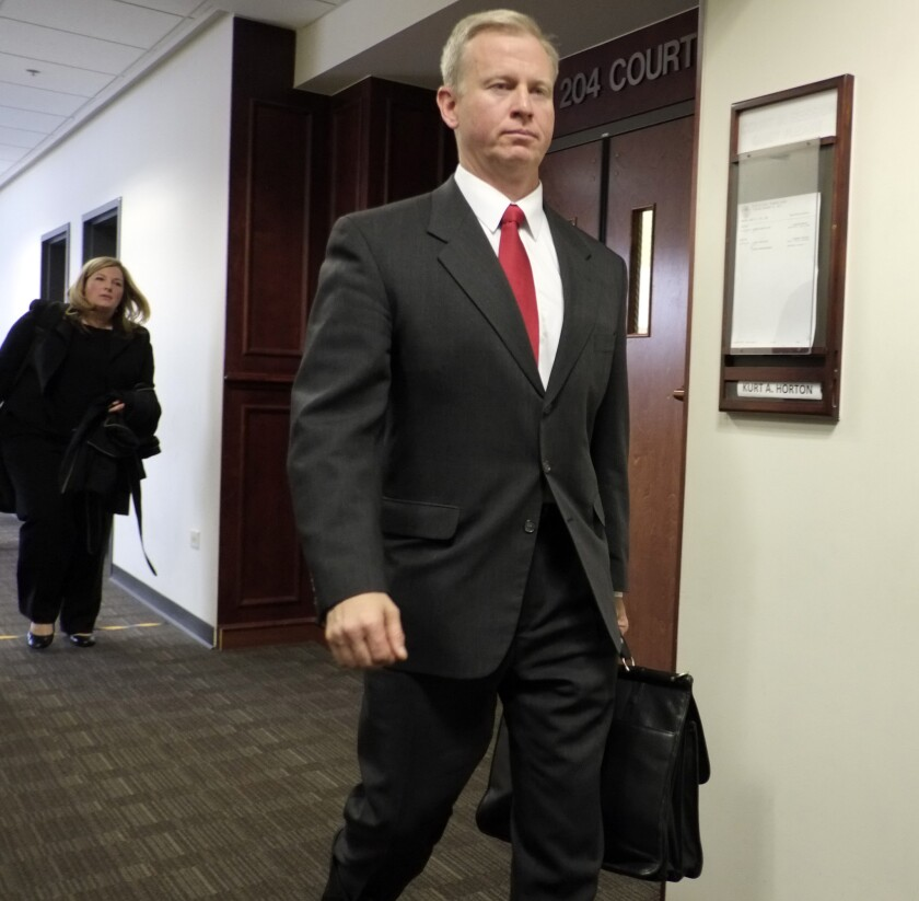District Atty. George Brauchler leaves district court in Centennial, Colo., after a hearing in the James Holmes case. Brauchler requested a second mental evaluation of Holmes. As a result, district judge Carlos A. Samour Jr. postponed the start of the trial, which had been scheduled for February.