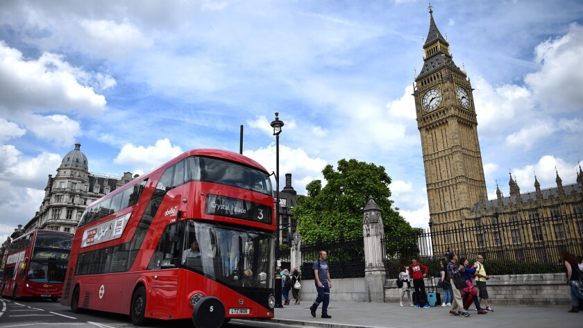 "Red buses travel past the Elizabeth Tower, center, which houses the ""Big Ben"" bell in the Palace of Westminster in central London. Airfares to Britain have dropped since the Brexit vote, a new study found."