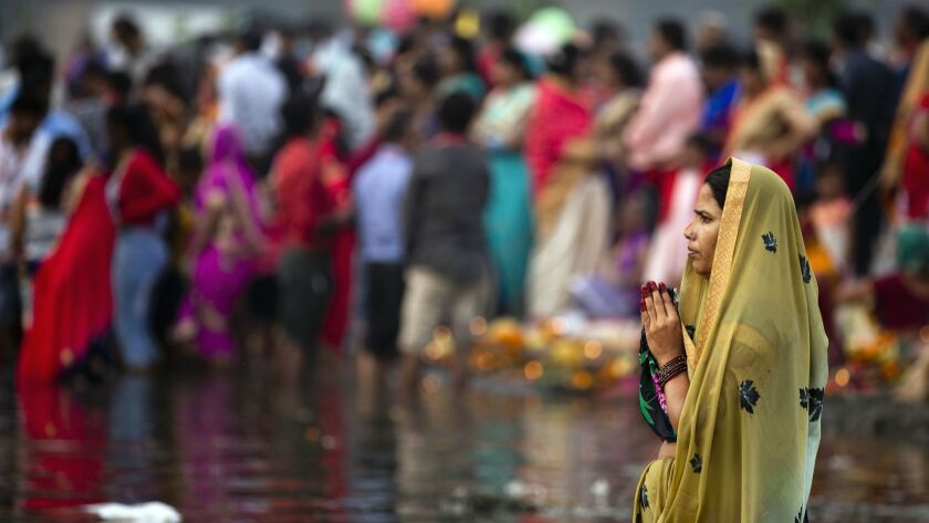 A Hindu devotee prays to the Sun god while standing in knee deep waters in River Yamuna during the C
