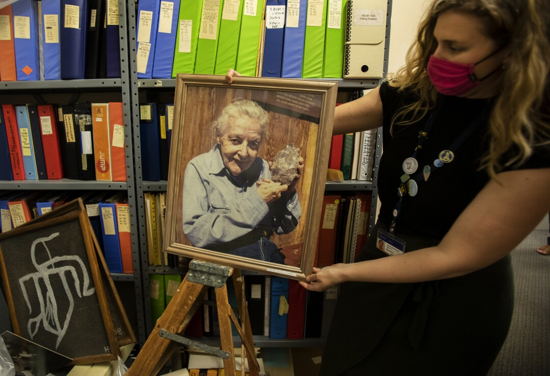 A woman displays a framed portrait of an older woman holding up an ancient stone tool