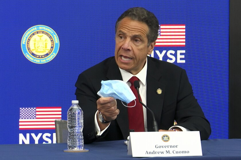 New York Gov. Andrew Cuomo holds a face mask while talking to the media at the New York Stock Exchange in March.