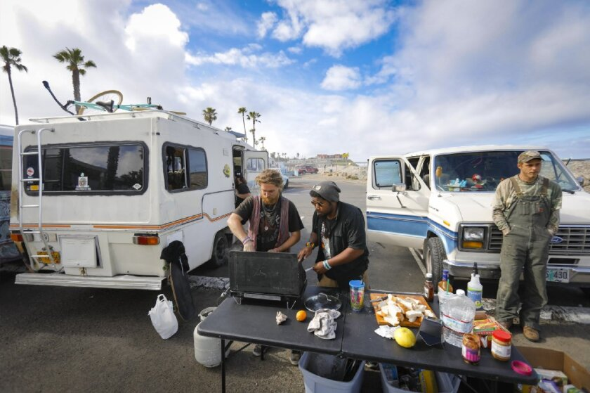Noodle, his street name, left, and Oak, his street name, center, make breakfast using a camping stove for people living in vehicles in the public parking lot near the Ocean Beach Lifeguard Station, as Noah, his street name, right, looks on.